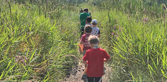 Arboretum campers walking through the prairie